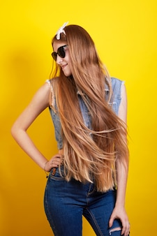 Long ginger girl in sunglasses poses on yellow background
