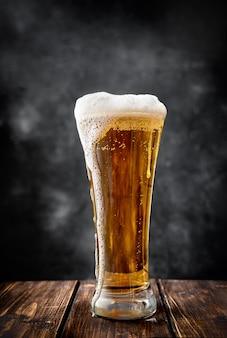 Длинный бокал пива на темном фоне