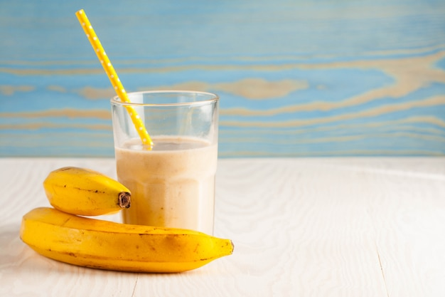 Длинные стаканы молочных коктейлей с шоколадом, клубникой, бананом, с мороженым на белом