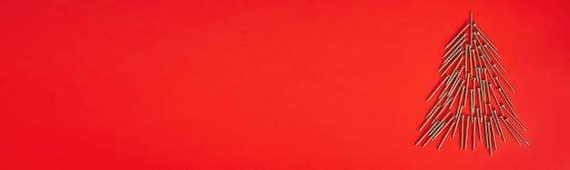 빨간색 배경에 크리스마스 트리 모양으로 배치된 긴 황금 셀프 태핑 나사. 배너, 복사 공간