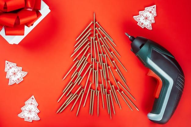 빨간색 배경에 크리스마스 트리, 드라이버 및 선물 상자 모양으로 배치된 긴 황금 셀프 태핑 나사
