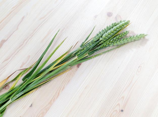 Длинные зеленые колосья пшеницы, лежащие на белой деревянной доске по диагонали, крупным планом