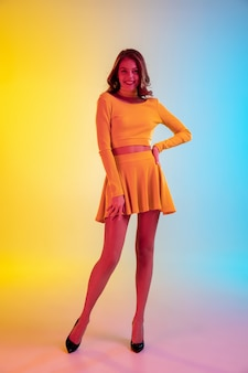 Capelli lunghi. bella ragazza seducente in vestito alla moda su sfondo giallo-blu sfumato in luce al neon.