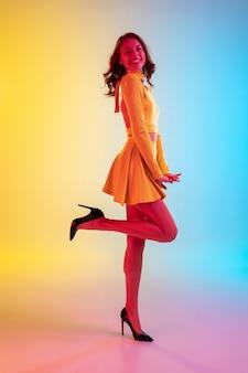 긴 머리. 네온 불빛에 그라데이션 노란색 파란색 배경에 유행 드레스에 아름 다운 매혹적인 소녀.