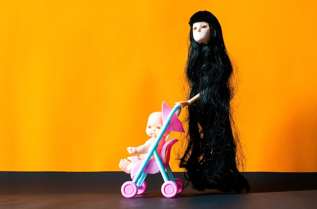 Long hair female flying ghost doll with her baby in a stroller on orange and black background. minimal halloween scary concept.