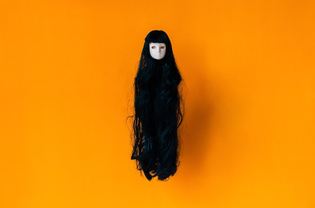 Long hair female ghost doll flying on orange background. minimal halloween scary concept.