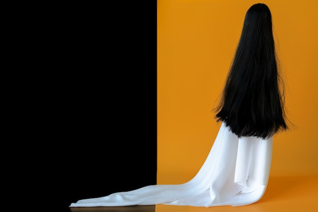 Long hair female ghost with white sheet costume with black and orange background. minimal halloween scary.