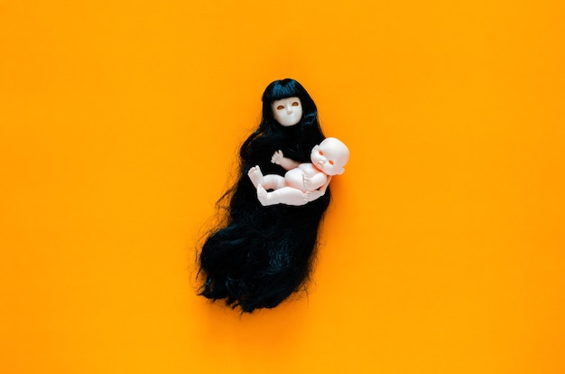 Long hair flying female ghost doll carries her baby on orange background. minimal halloween scary concept.