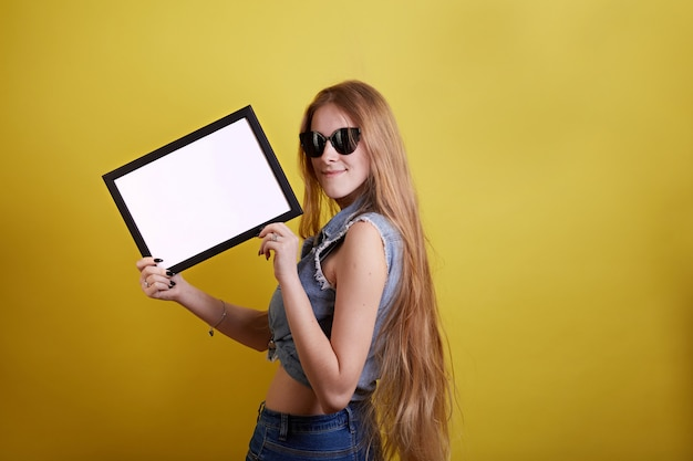 Long hair girl in glasses with empty frame on yellow background