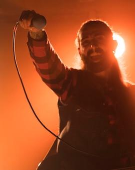 Uomo capelli lunghi che tiene il microfono