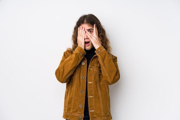Человек с длинными волосами, позирующий изолированно, моргает сквозь пальцы испуганно и нервно.