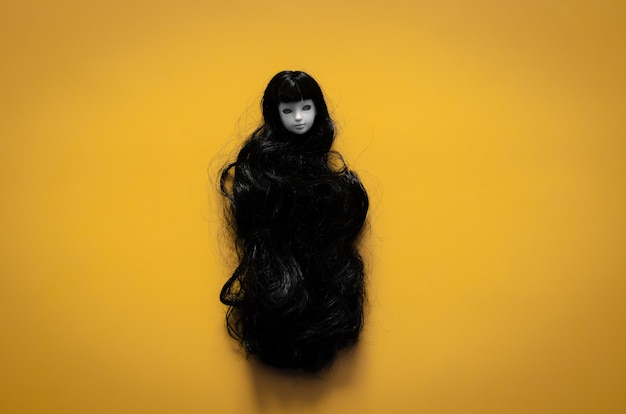 Long hair smiling female ghost doll on yellow background. minimal halloween scary concept.