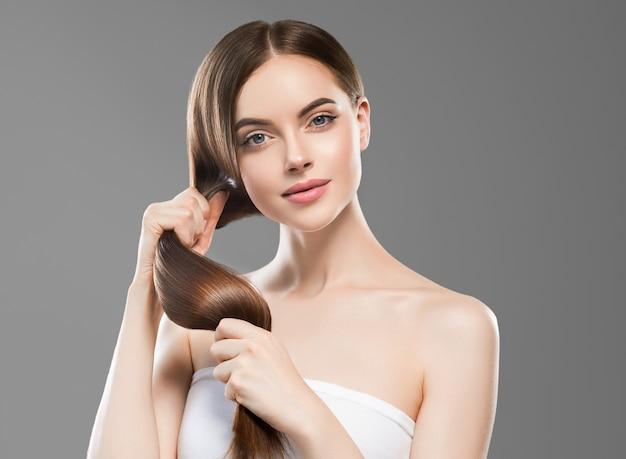 Длинные волосы женщина рука трогательно волосы гладкая брюнетка прическа модель