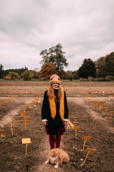 Long haired blindfolded girl standing in autumn field with cat sitting  near her legs.
