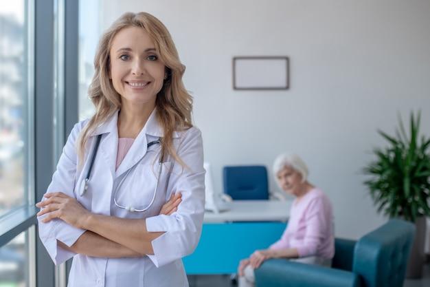 Длинноволосый белокурый доктор стоит со скрещенными руками и улыбается