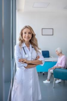 Длинноволосая блондинка-врач, стоящая со скрещенными руками