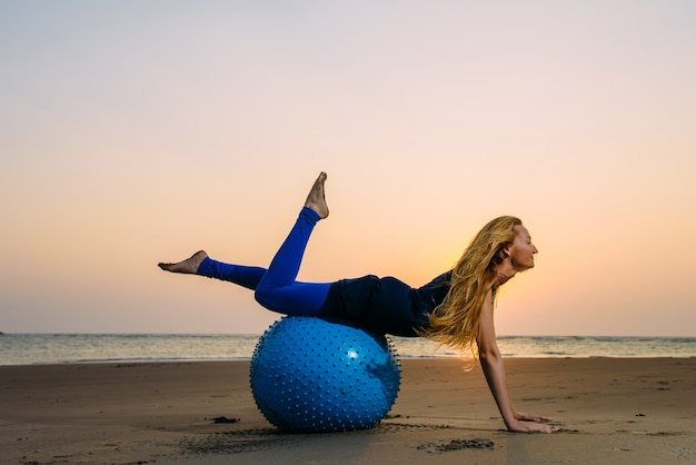 Long-haired blonde is engaged in pilates on a training ball on the beach during sunset. fit woman stretching her body using fitness ball. concept of health.