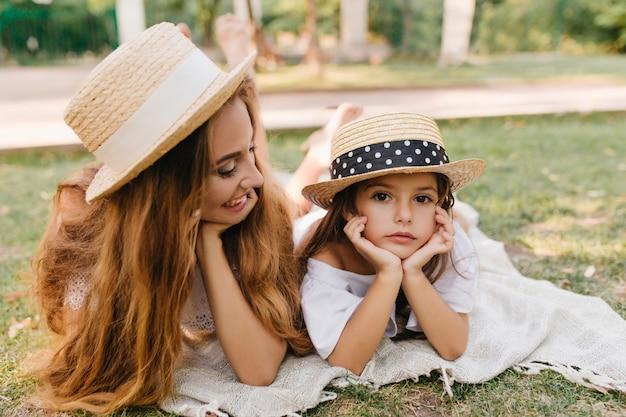 物思いにふける小さな娘を笑顔で見ているトレンディなカンカン帽の長い髪のブロンドの女性。ゲームの後に草の上で冷やしながら手で顔を支える黒いリボンと麦わら帽子の魅力的な女の子。