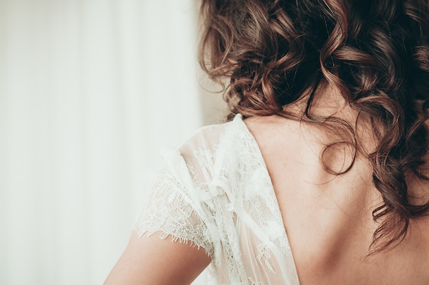Long haired brunette bride in unbuttoned white dress a closeup view from the back