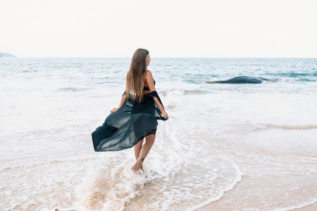A long-haired brunette walking on the beach