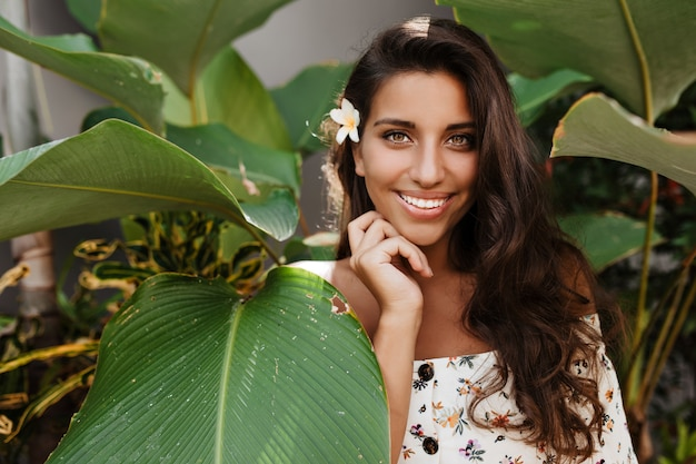 좋은 분위기의 긴 머리 갈색 머리 여자는 열대 식물 사이에서 미소로 포즈