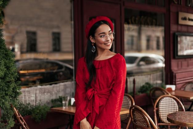 빨간 베레모, 세련된 드레스, 안경을 쓴 긴 머리의 갈색 머리 여성은 진심으로 웃고 밖에서 좋은 분위기로 포즈를 취합니다.
