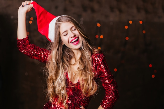 Long-haired brunette woman taking off santa claus hat