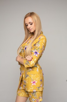Длинноволосая белокурая женщина кавказа в желтом костюме, стоя со скрещенными руками. концепция моды
