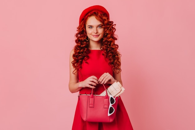 Long-haired cute lady in red hat and bright dress posing on pink space. woman with blue eyes holds leather bag, magazine and glasses.