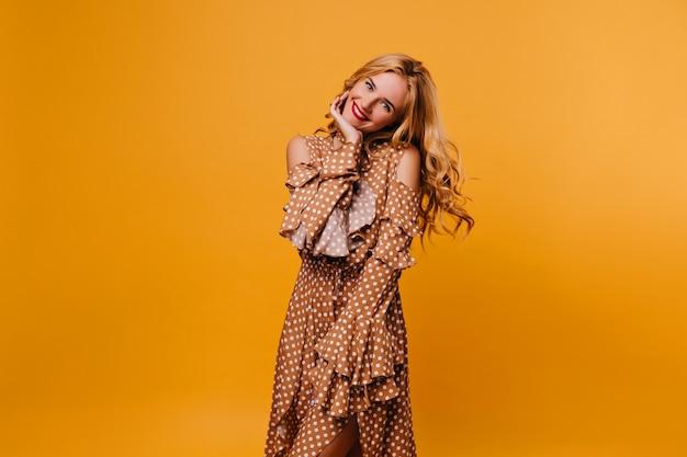 Длинноволосая женская модель позирует с милой улыбкой на желтой стене. блаженная кавказская девушка в длинном коричневом платье смеется