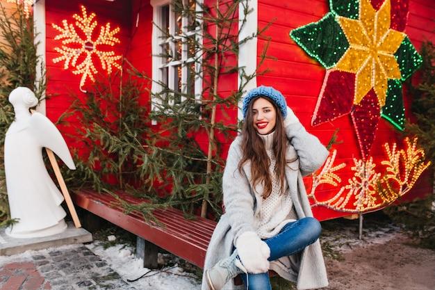 Длинноволосая женская модель сидит на деревянной скамейке возле красного дома, украшенного на рождество. привлекательная брюнетка девушка позирует после новогоднего праздника рядом с зелеными деревьями и скульптурами ангела.