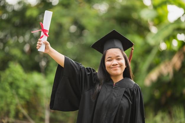Long haired female students wearing black ruffle dresses expressing joy on graduation at the university.