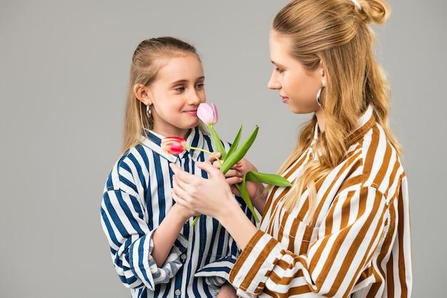 両方がそれを運んでいる間花を共有している明るい服を着た長い髪の完璧な女性
