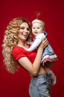손에 긍정적 인 아기 딸과 함께 서있는 동안 그녀의 혀의 끝을 보여주는 장발 재미 있은 여자
