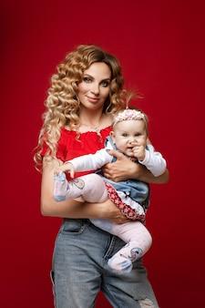 긍정적인 아기 딸을 손에 들고 서 있는 동안 혀 끝을 보여주는 긴 머리의 재미있는 여성