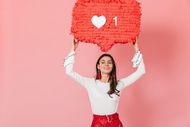 Длинноволосая девушка в красных серьгах с улыбкой демонстрирует огромный лайк в instagram. портрет женщины в белой блузке на розовом фоне.