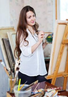 Длинношерстная девушка рисует на мольберте