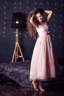 Long-haired girl in pink dress on dark with bokeh
