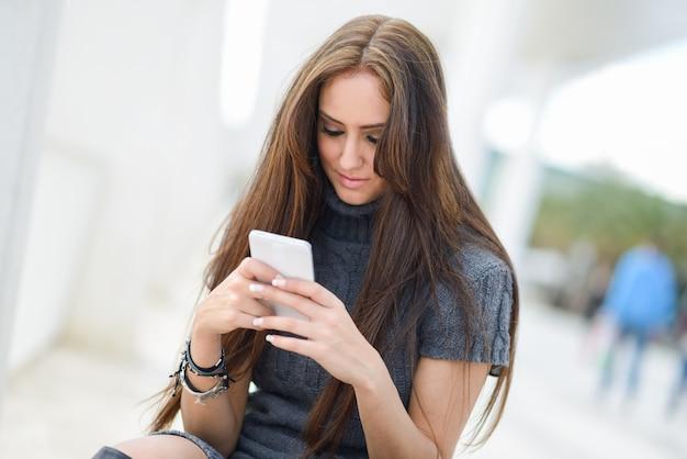 彼女の携帯電話でテキストメッセージ長い髪の少女