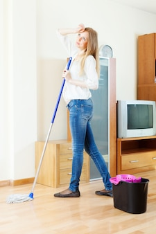 Long-haired girl washing parquet floor with mop