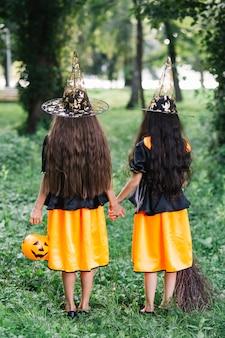 Длинношерстные девушки в колдовских костюмах, держась за руки