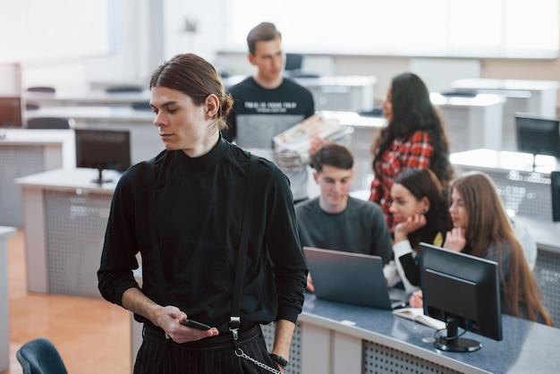 長い髪の男。近代的なオフィスで働くカジュアルな服装の若い人たちのグループ