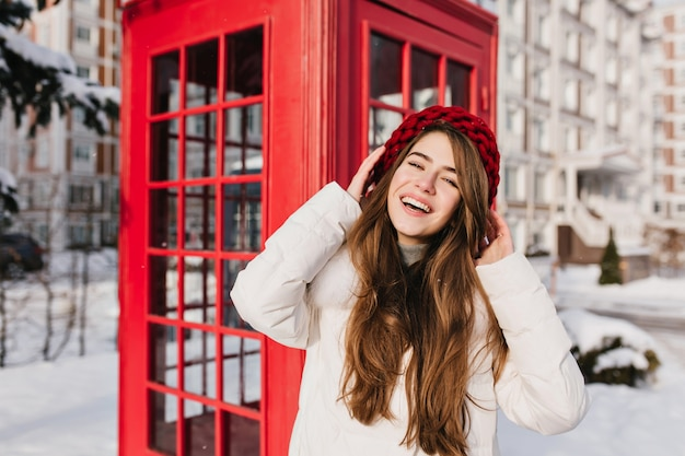 Long-haired lady in knitted beret posing with smile beside phone booth in cold day. outdoor photo of charming brunette woman in red hat standing near call-box in winter morning.