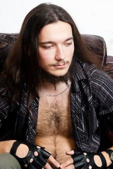 의자에 털이 많은 가슴을 가진 장발 남자