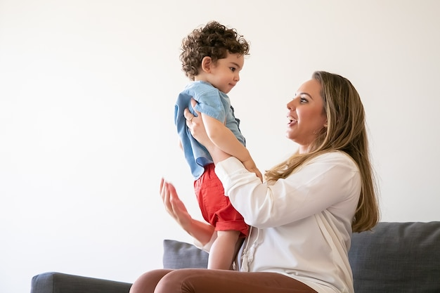 Длинноволосая мать держит маленького мальчика, разговаривает с сыном и сидит на диване. серьезный малыш стоит на коленях мамы и внимательно ее слушает. семейное время, материнство и концепция выходных