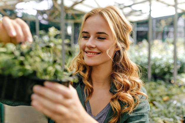 Long-haired redhead girl is happy and sincerely smiling, holding pot of greens in her hands. closeup portrait outside surrounded by plants.