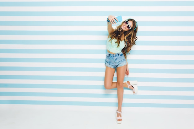 Long-haired tanned girl wearing denim shorts and heeled sandals standing on one leg and making selfie with smile. full-length portrait of young woman in sunglasses posing on striped wall.
