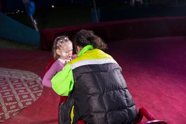 長い髪の先生または父親が小さな女の子が演劇のメイクアップの準備をするのを手伝っています、後部