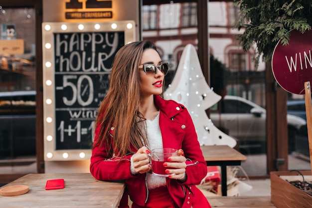 Long-haired woman in black sunglasses standing on the street with cup of tea