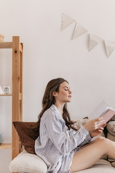 Long-haired woman in blue shirt sits on couch and reads book